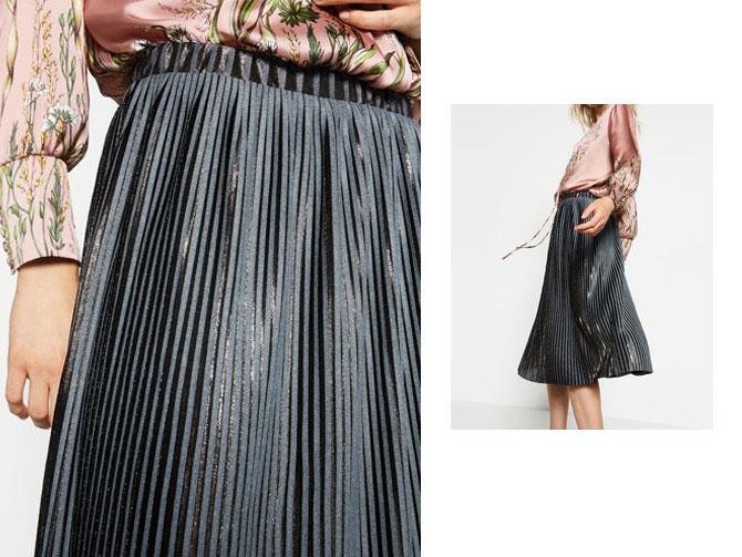 Falda plisada gris metalizada con blusa estampada de Zara.