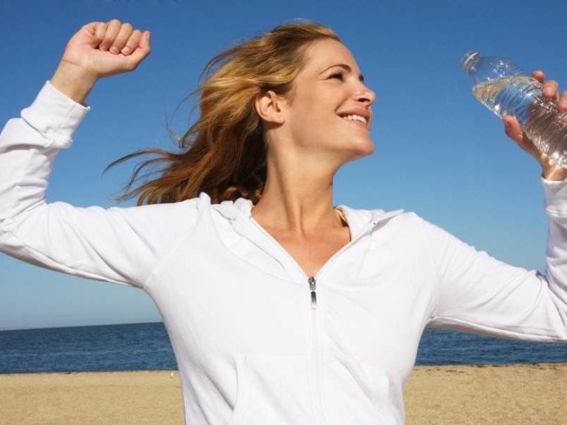 mujer madura contenta en la playa hidratándose con agua